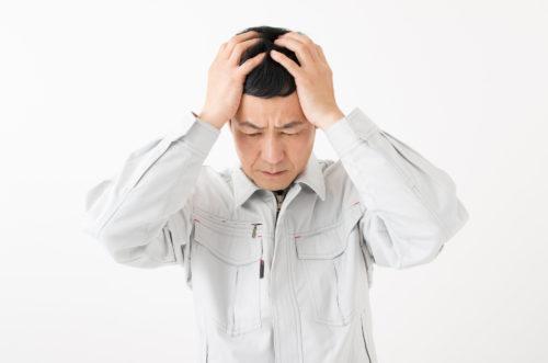 頭を抱える作業服の男性