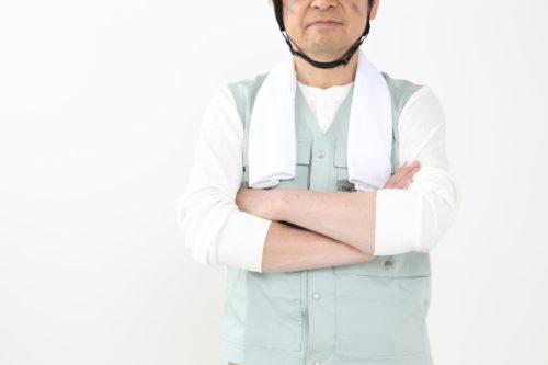 腕組みをする作業着の男性