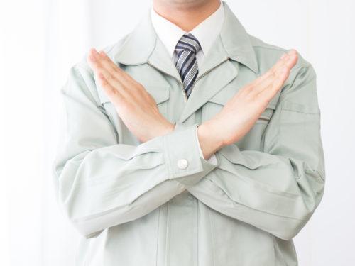 胸の前でバツを作る作業服の男性