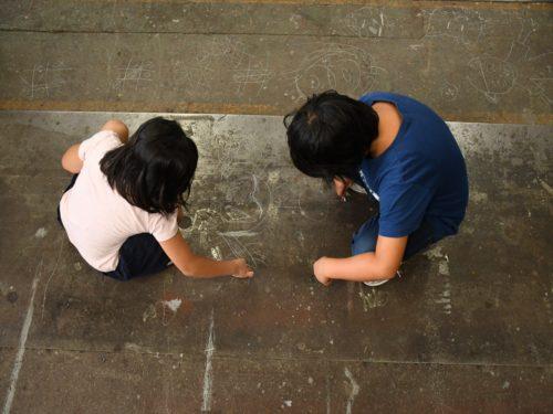アスファルトでの落書きを楽しむ子供たち