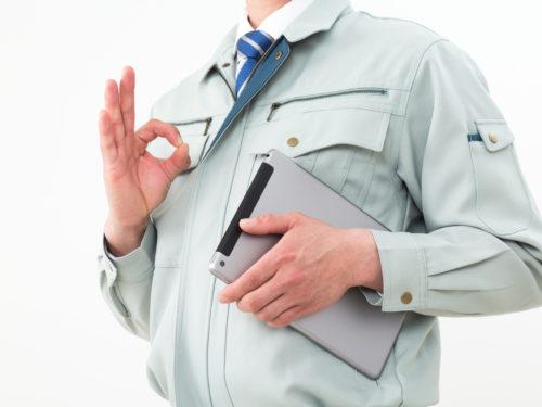 指で丸をつける作業服の男性